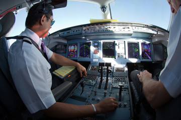 Cockpit of jet aircraft in flight. The pilots of the passenger plane at work. Wall mural