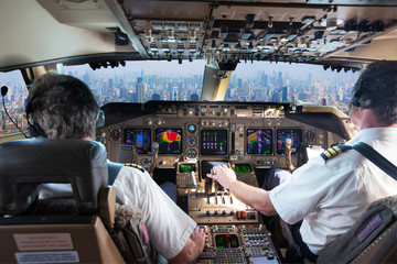 The cockpit of a modern passenger aircraft in flight. Pilots at work. A view from the cockpit to the skyscrapers of the business center of a huge city. Wall mural