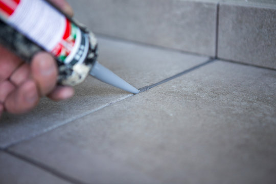 The hand of a construction worker filling the gap between ceramic tiles with silicone