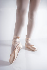 legs and feet with pink satin pointe shoes by a classical dancer posing