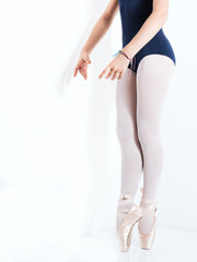 legs and feet with pink satin pointe shoes by a classic ballerina on tiptoe