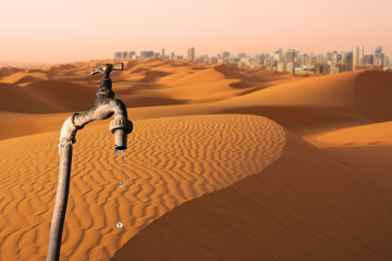 Dripping faucet, desert and skyline of big city in the background