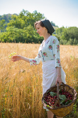 Woman in 40s clothes walks in the Italian countryside, next to a wheat field, carrying a basket of cherries