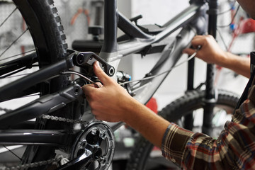 Cropped shot of male mechanic working in bicycle repair shop, repairman fixing bike in a workshop, wearing protective workwear