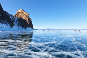 Winter landscape of frozen Baikal Lake. Olkhon Island. Many tourists come to visit the famous Cape Khoboy for a walk on ice, skate and take a picture