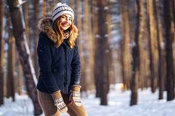 Portrait of young beautiful girl with long hair, in a blue jacket and knitted hat and mittens posing in sunny winter day. Fashion young woman in the winter forest. Christmas, winter holidays concept.  Wall mural