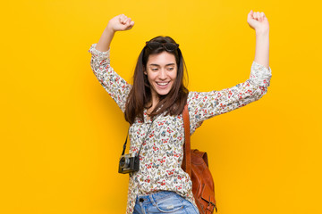 Young brunette traveler woman celebrating a special day, jumps and raise arms with energy.