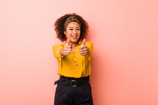 Young african american woman against a pink background with thumbs ups, cheers about something, support and respect concept.