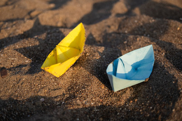 Closeup top view of two small cute yellow and blue paper ships standing on sandy sunny sunrise or sunset beach near sea water. Travel concept. Horizontal color photography.