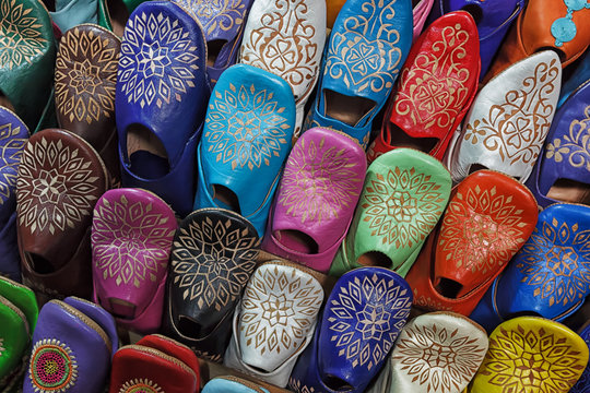 Colourful moroccan babouches displayed on a wall shelf.