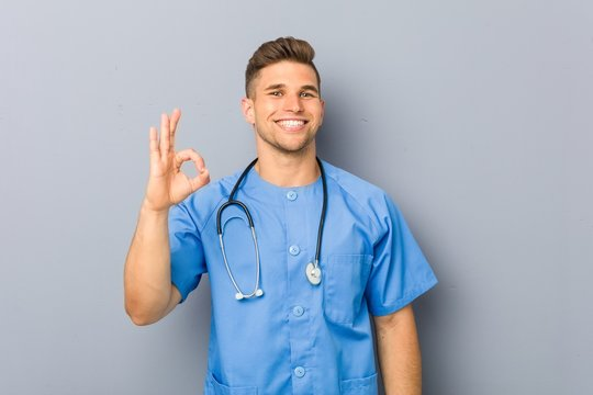 Young nurse man cheerful and confident showing ok gesture.