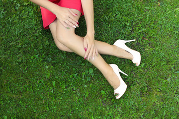 Multicolored fashionable manicure and pedicure for girls in white high-heeled sandals on a background of green grass.