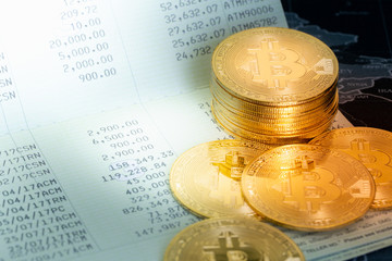 Stack of golden Bitcoins on bank passbook. Savings and investing in virtual currency and cryptocurrency concept.