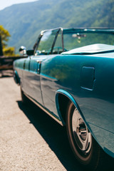 Color detail a vintage car sky blue color and shiny chrome, selective focus, turquoise, vertical photo