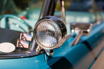 Printed roller blinds Vintage cars Color detail on the headlight of a vintage car sky blue color and shiny chrome, selective focus, turquoise