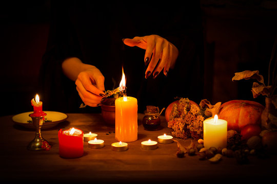 Witch burns a herb on the altar in the dark. Female hands with sharp black nails do magic among candles, pumpkin, nuts, dry leaves, selected focus, low key