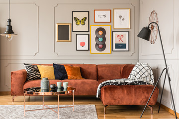 Gallery of trendy posters in elegant grey living room interior with brown corner sofa