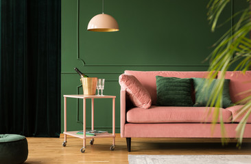 Stylish velvet sofa in pink and green living room