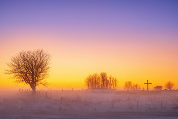 Misty sunset at a religious cross in cold weather
