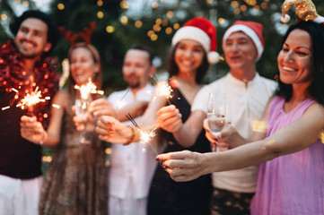 Group of friends celebrating Christmas with sparkles and champagne Wall mural