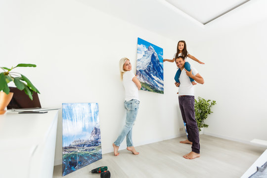 family hangs a large photo canvas at home