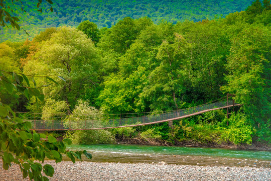 Iron pedestrian suspension bridge over the Belaya river. Republic Of Adygea, Russia.