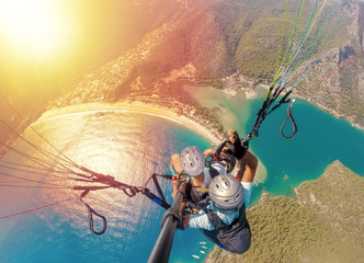 Extreme sport. Landscape .Paragliding in the sky. Paraglider tandem flying over the sea with blue water and mountains in bright sunny day. Aerial view of paraglider and Blue Lagoon in Oludeniz, Turkey Wall mural