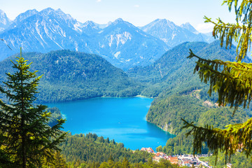 Landscape of Alpine mountains, Germany. Beautiful scenic view of nature from above. Nice landscape with Alpsee lake and Hohenschwangau village in forest. Scenery of Bavarian Alps in summer.