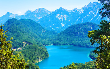 Aluminium Prints Blue Landscape of Alpine mountains, Germany. Panoramic scenic view of nature from above. Perfect landscape with Alpsee lake in summer. Beautiful scenery of Bavarian Alps with green forest and blue peaks.