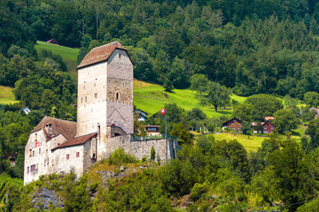 Fototapete - Sargans castle in Alps, Switzerland. It is landmark of St Gallen canton. Scenic view of old castle on background of mountain forest and village. Alpine landscape with Swiss medieval castle in summer.