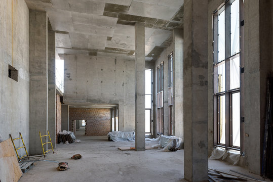 Construction of large building. Inside the modern construction site. Contemporary structure under construction with concrete walls, pillars, ceiling and floor. Concept of building business.