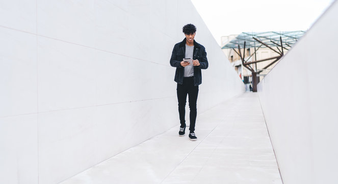 Full length portrait of happy stylish Latino hipster guy updating profile in social networks while walking at city urban setting and using 4g wireless for browsing, trendy man with touch pad
