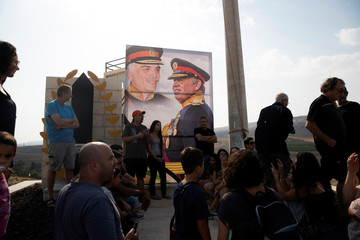 "A picture of Jordanian King Abdullah and his father, the late King Hussein, is seen as people visit the ""Island of Peace"" in an area known as Naharayim in Hebrew and Baquora in Arabic, on the Jordanian side of the border with Israel"
