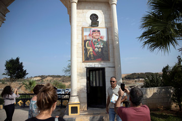 "A picture of Jordan's King Abdullah is seen as people return after visiting the ""Island of Peace"" in an area known as Naharayim in Hebrew and Baquora in Arabic, on the Jordanian side of the border with Israel"