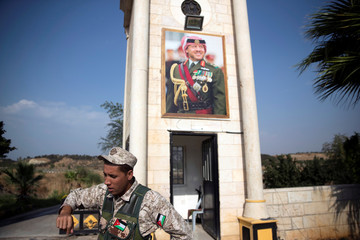 "A Jordanian soldier stands near the ""Island of Peace"" in an area known as Naharayim in Hebrew and Baquora in Arabic, on the Jordanian side of the border with Israel"