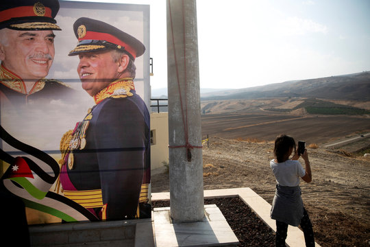 "A picture of Jordanian King Abdullah and his father, the late King Hussein, is seen as a girl visits the ""Island of Peace"" in an area known as Naharayim in Hebrew and Baquora in Arabic, on the Jordanian side of the border with Israel"