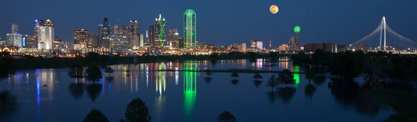 Dallas skyline reflecting in river with full moon