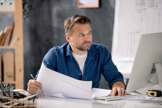 Serious bearded engineer with papers looking at computer screen by workplace