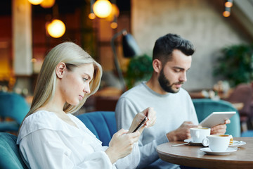 Serious blonde girl and her boyfriend using mobile gadgets by table in cafe