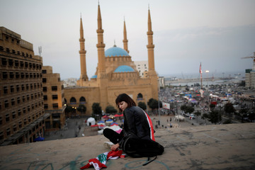 """A woman sits on the roof of an abandoned cinema known as """"The Egg"""", with Mohammad Al-Amin mosque in the background, in Beirut"""