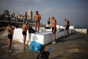 Men dry themselves after swimming on a beach of Beirut