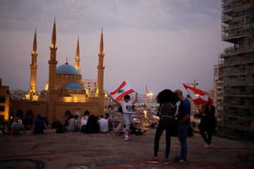 """People hold Lebanese flags as they pose for pictures on the top of an abandoned cinema known as """"The Egg"""", with Mohammad Al-Amin mosque in the background, in Beirut"""