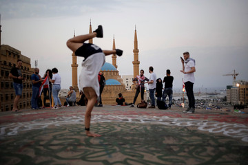 """A youth practises break dance on the roof of an abandoned cinema known as """"The Egg"""", with Mohammad Al-Amin mosque in the background, in Beirut"""