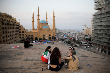 """A group of women sit on the roof of an abandoned cinema known as """"The Egg"""", with Mohammad Al-Amin mosque in the background, in Beirut"""