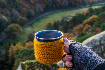 Woman hand wearing knitted fingerless gloves holding a cozy crochet mug with hot tea on a cold autumn day in a mountain background.
