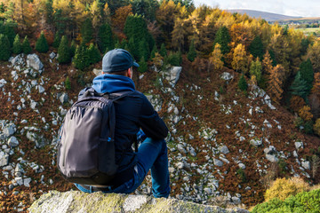 Male hiker resting on the mountain top looking at the autumn colored trees across the valley. Rocky mountainous fall landscape.