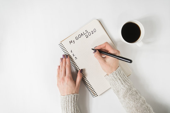 Female hands writing My Goals 2020 in a notebook. Mug of coffee on the table, top view