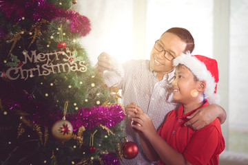 Boy and father decorating a Christmas tree