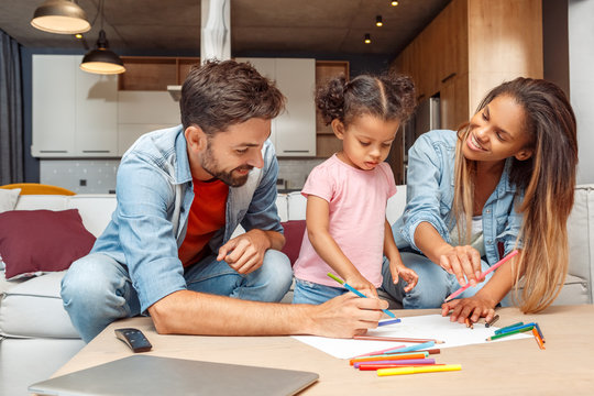 Mixed Race Family. Mother father and daughter sitting on sofa at living room drawing together early development smiling cheerful