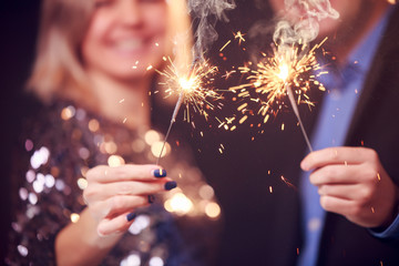 Picture of happy couple with sparklers on black background